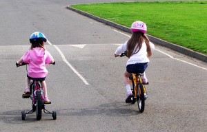 2 children on bikes, one with stabilisers, one without